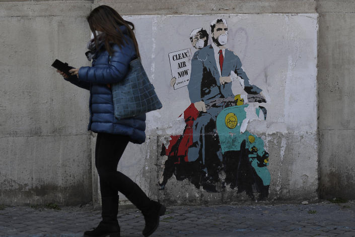 """FILE - In this file photo dated Friday, April 9, 2021, a woman walks past a poster depicting a scene from the famed movie """" Roman Holiday"""" with Gregory Peck and Audrey Hepburn wearing surgical masks as riding a Lambretta scooter in Rome. The return of international travel is key to economic recovery across Europe, particularly for countries that rely more heavily on tourism, according to figures released Thursday June 24, 2021, from the World Travel and Tourism Council. (AP Photo/Gregorio Borgia, FILE)"""