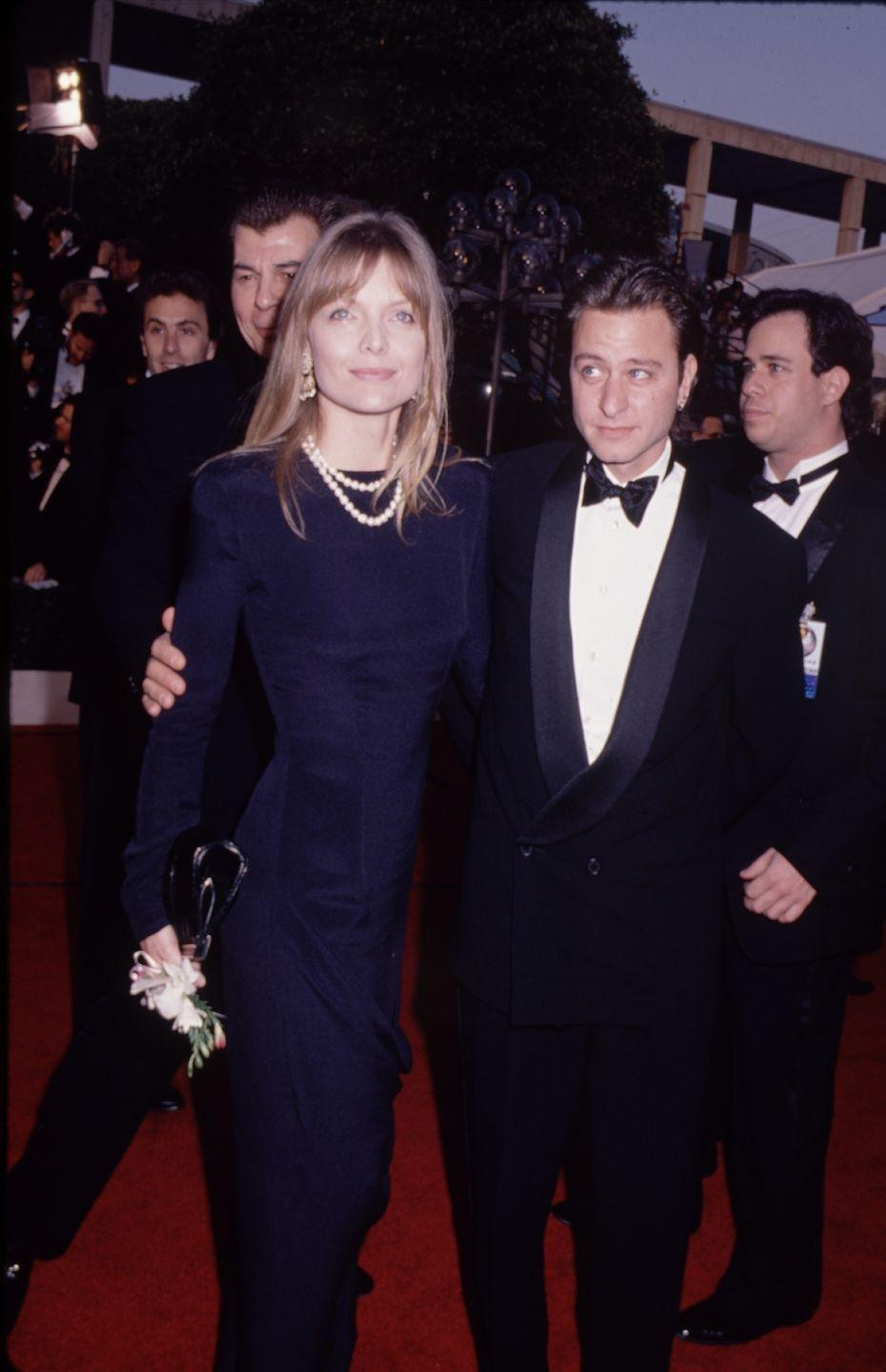 <p>Michelle's navy blue gown, pearls and (inexplicable) flowers in hand were a vision of grace. She rocked the Oscar's that year with a nomination for Best Actress in <em>The Fabulous Baker Boys.</em></p>