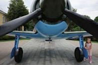 A girl stands under a Soviet-style military airplane at Kremlin in Nizhny Novgorod, Russia, June 30, 2018. REUTERS/Damir Sagolj