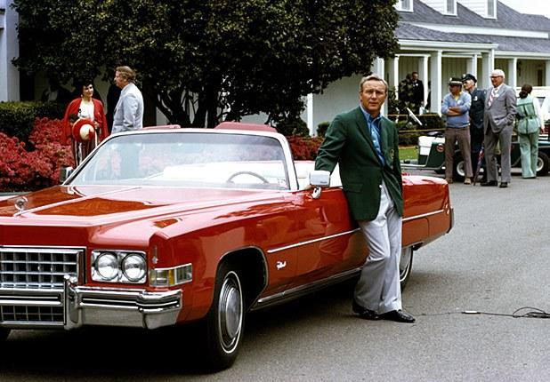 Palmer leans on a red Cadillac in his green jacket during the 1973 Masters Tournament.