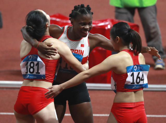 Bahrain's Edidiong Odiong, centre, is congratulated by China's Wei Yongli and Liang Xiaojing, right, after winning the women's 100m final during the athletics competition at the 18th Asian Games at Gelora Bung Karno Stadium in Jakarta, Indonesia, Sunday, Aug. 26, 2018. (AP Photo/Dita Alangkara)