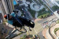 Lai Chi-wai, a paraplegic climber, attempts to climb the 320-metre tall Nina Tower using only his upper body strength, in Hong Kong