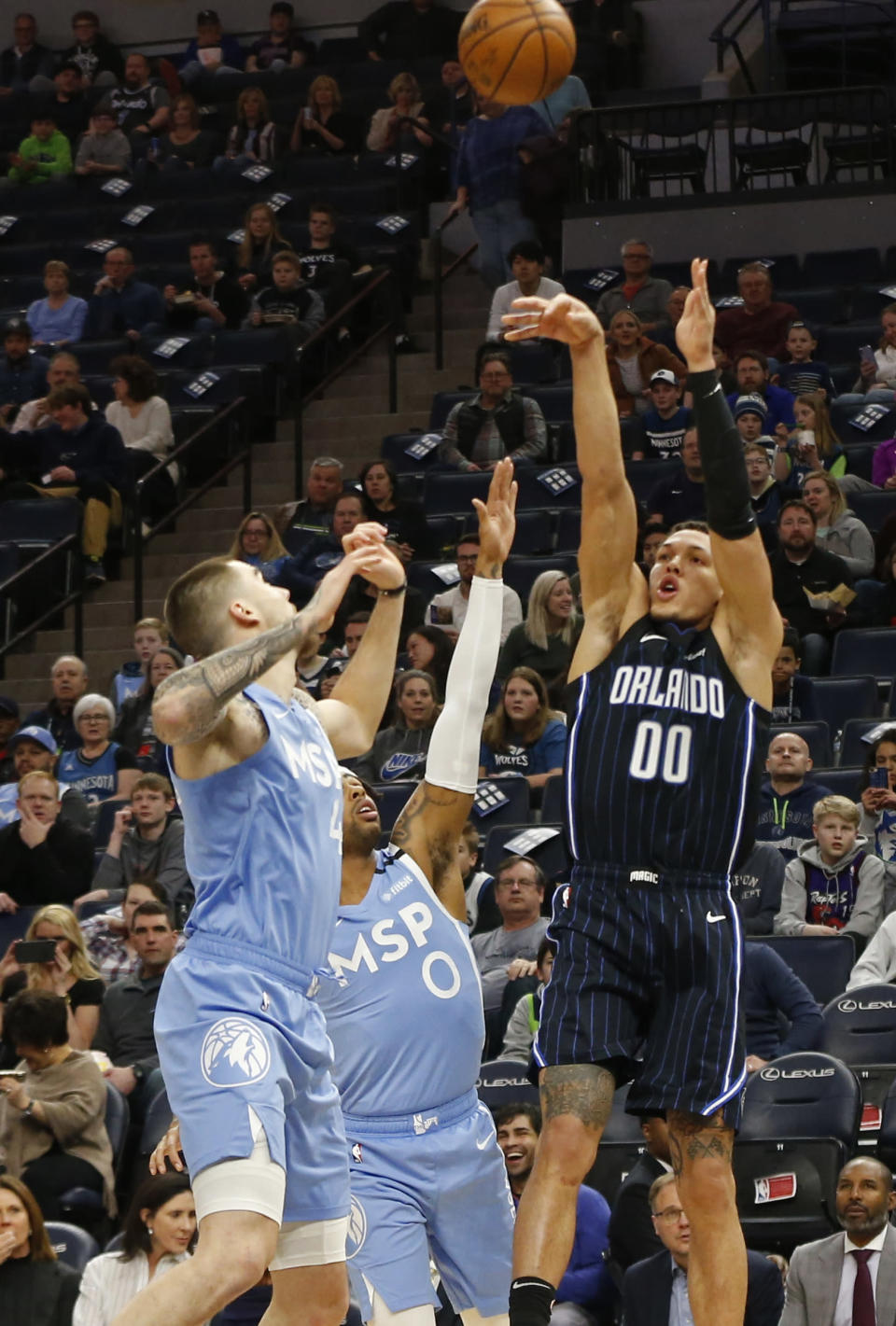 Orlando Magic's Aaron Gordon, right, shoots past Minnesota Timberwolves' Juancho Hernangomez, left, and D'Angelo Russell in the first half of an NBA basketball game, Friday, March 6, 2020, in Minneapolis. (AP Photo/Jim Mone)