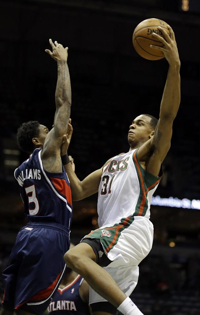Milwaukee Bucks' John Henson (31) puts up a shot against Atlanta Hawks' Louis Williams (3) during the second half of an NBA basketball game Saturday, Jan. 25, 2014, in Milwaukee. (AP Photo/Jeffrey Phelps)