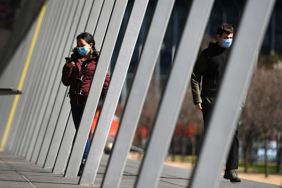 A woman arrives at a vaccination centre in Melbourne during the city's sixth lockdown as it battles an outbreak of Covid-19 coronavirus.