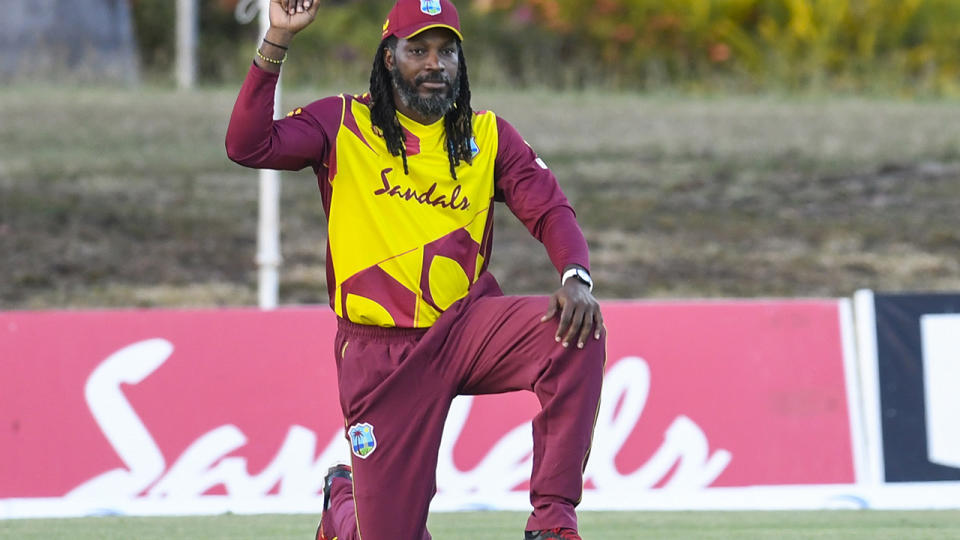 Chris Gayle kneels prior to a cricket match for the West Indies.