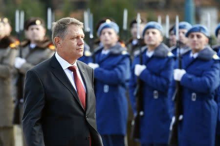 Romania's new President Klaus Iohannis walks in front of the honour guard during a take-over ceremony at Cotroceni presidential palace in Bucharest December 21, 2014. REUTERS/Bogdan Cristel
