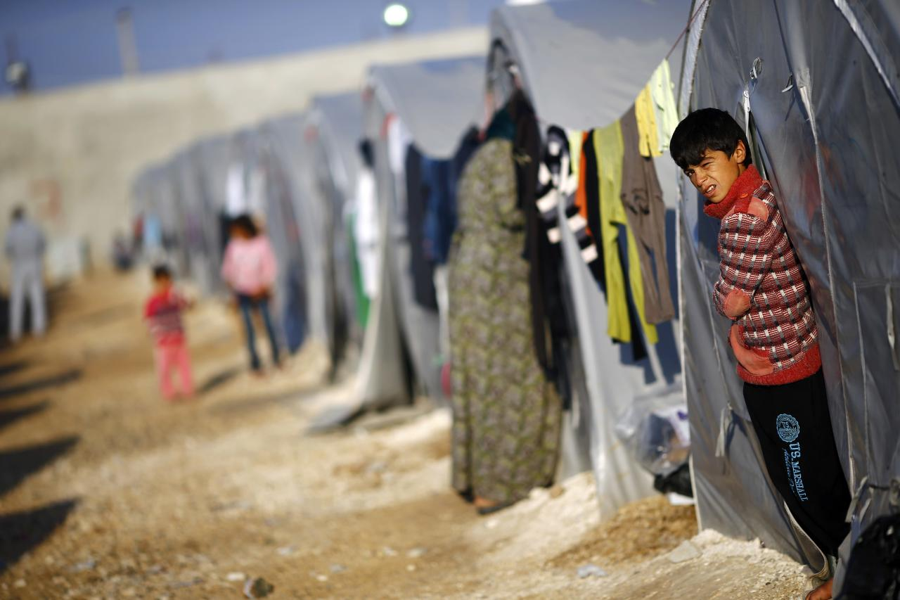 A Kurdish refugee boy from the Syrian town of Kobani stands outside his tent in a camp in the southeastern town of Suruc, Sanliurfa province October 22, 2014. REUTERS/Kai Pfaffenbach (TURKEY  - Tags: MILITARY CONFLICT POLITICS)