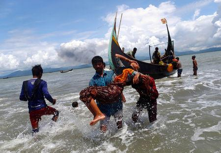 Smoke is seen on Myanmar's side of border as an exhausted Rohingya refugee woman is carried to the shore after crossing the Bangladesh-Myanmar border by boat through the Bay of Bengal, in Shah Porir Dwip, Bangladesh September 11, 2017. REUTERS/Danish Siddiqui