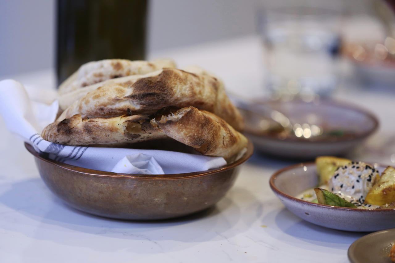 In this photo taken June 20, 2018, a bowl of fresh pita bread made by guest chef Muna Anaee, a refugee from Iraq, beckons from a dining table at Tawla Restaurant in San Francisco during the inaugural Refugee Food Festival. San Francisco restaurants are opening their kitchens for the first time to refugees who are showcasing their culinary skills and native cuisines while raising their profiles as aspiring chefs as part of a program to increase awareness about the plight of refugees worldwide. (AP Photo/Lorin Eleni Gill)