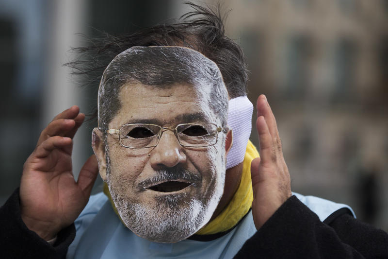 A man covers his face with a mask of Egypt President Mohammed Morsi during a protest in front of the chancellery against the visit of Morsi prior to a meeting of him with German Chancellor Angela Merkel in Berlin, Germany, Wednesday, Jan. 30, 2013. (AP Photo/Markus Schreiber)