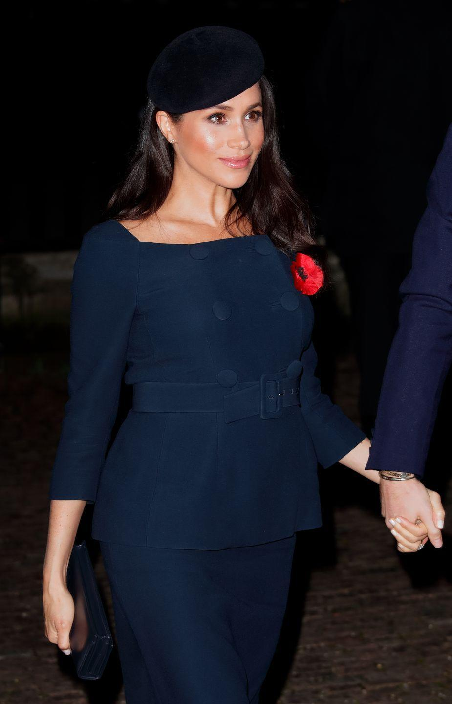 """<p>The royal wore a navy peacoat dress with bateau neckline - similar to her <a href=""""https://www.net-a-porter.com/gb/en/Shop/Designers/Givenchy?pn=1&npp=60&image_view=product&dScroll=0"""" rel=""""nofollow noopener"""" target=""""_blank"""" data-ylk=""""slk:Givenchy"""" class=""""link rapid-noclick-resp"""">Givenchy</a> wedding dress silhouette - accessorised with a velvet fascinator. </p><p>The ensemble was reminiscent of the pink <a href=""""https://www.net-a-porter.com/gb/en/Shop/Designers/Prada?pn=1&npp=60&image_view=product&dScroll=0"""" rel=""""nofollow noopener"""" target=""""_blank"""" data-ylk=""""slk:Prada"""" class=""""link rapid-noclick-resp"""">Prada</a> look she wore back in June 2018 when she attended the Queen's Young Leaders Awards.</p>"""