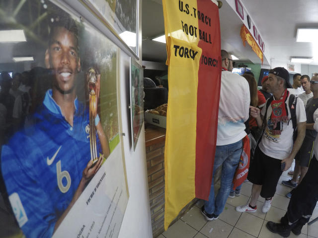 In this Saturday, April 25, 2018 photo, customers line up for refreshments in the canteen of the club, US Torcy, east of Paris, France, where France midfielder Paul Pogba played when he was a teenager. Not all the money that will change hands after the World Cup, when clubs trade players who distinguish themselves on footballs biggest stage, will line the pockets of selling clubs, agents and the players themselves. A sliver of the wealth will also trickle down to footballs grassroots, to unpretentious, volunteer-run clubs where kids take first steps toward their dreams of making a career in the sport. (AP Photo/John Leicester)