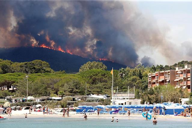 <p>Flames and smoke fill the sky above a burning hillside as tourists swim on the beach in Bormes-les-Mimosas, in the Var department, France, July 26, 2017. (Jean-Paul Pelissier/Reuters) </p>