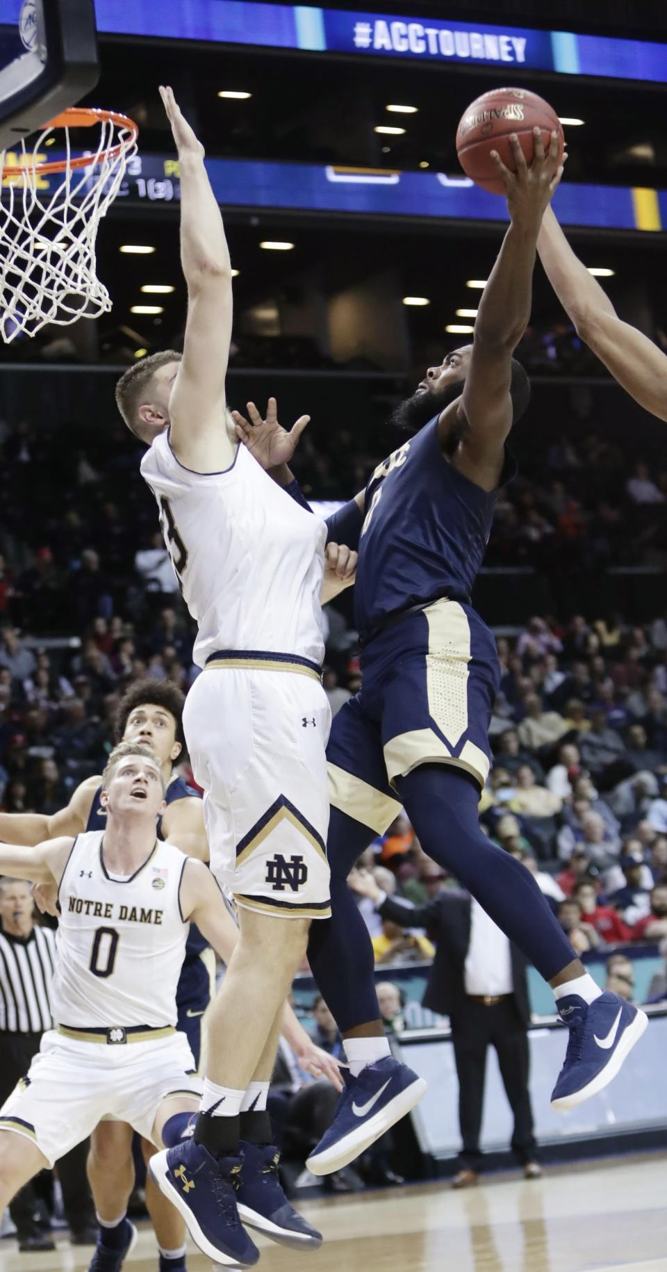 Pittsburgh's Jared Wilson-Frame (0) shoots over Notre Dame's Martinas Geben (23) during the first half of an NCAA college basketball game in the first round of the Atlantic Coast Conference tournament Tuesday, March 6, 2018, in New York. (AP Photo/Frank Franklin II)