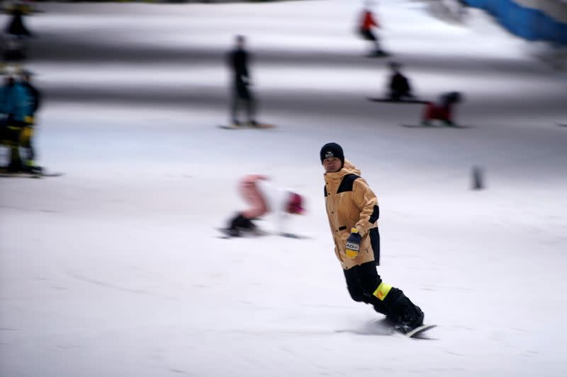 People snowboard inside an indoor ski park at Qiaobo Ice and Snow World in Shaoxing