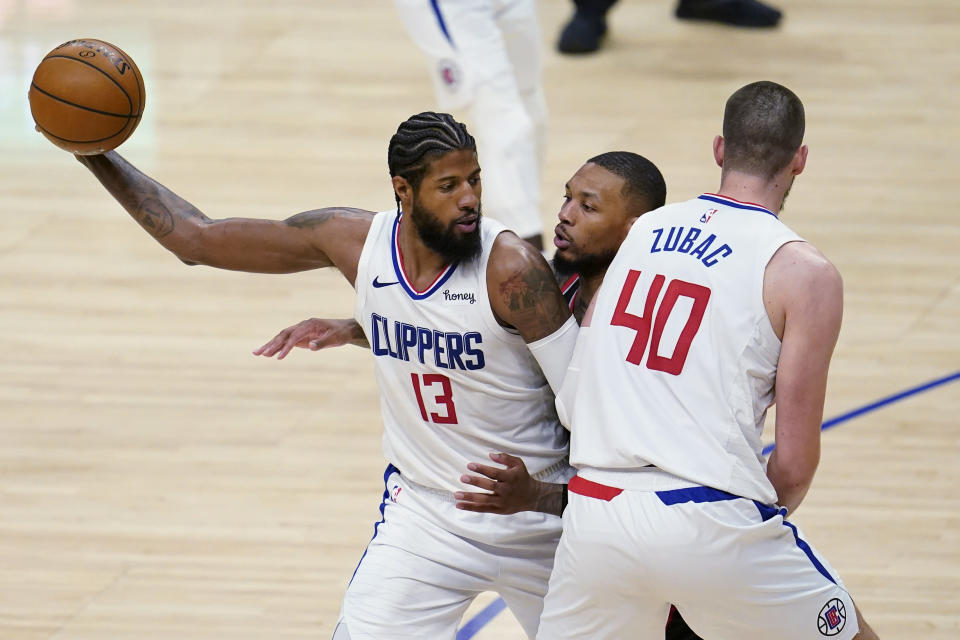 Los Angeles Clippers guard Paul George (13) holds the ball as Ivica Zubac (40) sets a screen on Portland Trail Blazers guard Damian Lillard, center, during the second half of an NBA basketball game Tuesday, April 6, 2021, in Los Angeles. (AP Photo/Marcio Jose Sanchez)