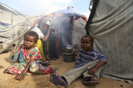 Hassan sits with her children outside her temporary dwelling after fleeing famine in Marka Lower Shebbele regions to the capital Mogadishu