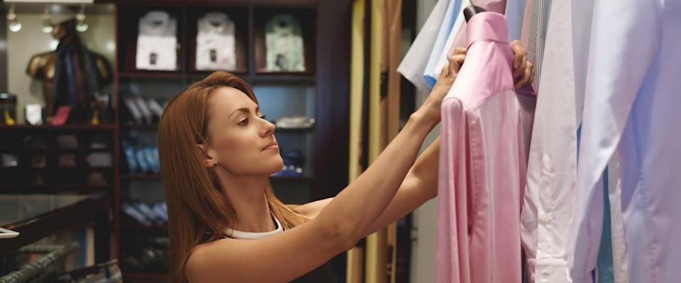 Personal shopper picking out dress shirts for a male client