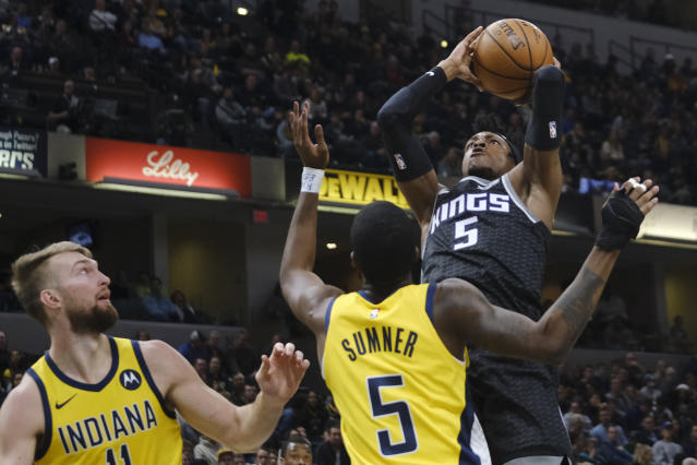 Sacramento Kings guard De'Aaron Fox, right, shoots over Indiana Pacers guard Edmond Sumner (5) during the first half of an NBA basketball game in Indianapolis, Friday, Dec. 20, 2019. (AP Photo/AJ Mast)