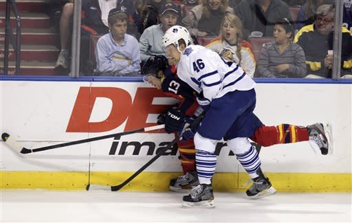 Florida Panthers' Mike Santorelli (13) and Toronto Maple Leafs' Joey Crabb (46) battle for the puck during the first period of an NHL hockey game in Sunrise, Fla., Tuesday, March 13, 2012. (AP Photo/J Pat Carter)