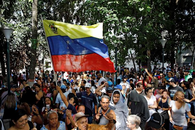 <p>People hold a national flag while gathering at a polling station during an unofficial plebiscite against Venezuela's President Nicolas Maduro's government and his plan to rewrite the constitution, in Caracas, Venezuela July 16, 2017. (Carlos Garcia Rawlins/Reuters) </p>