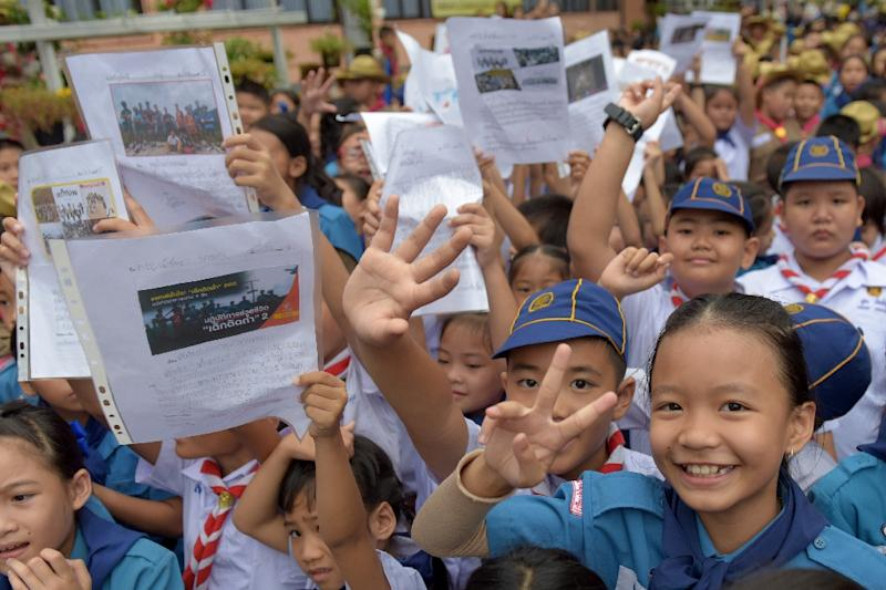 Thai students smile as they hold pictures of 12 boys and their fooball coach at a school in front of hospital where the boys rescued after being trapped in a nearby cave for 18 harrowing days have been brought for observation in Chiang Rai