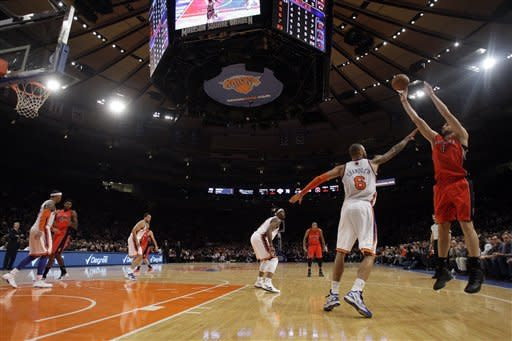 Toronto Raptors' Andrea Bargnani (7), of Italy, shoots over New York Knicks' Tyson Chandler (6) during the second half of an NBA basketball game Monday, Jan. 2, 2012, in New York. Bargnani scored 21 points as the Raptors won the game 90-85. (AP Photo/Frank Franklin II)