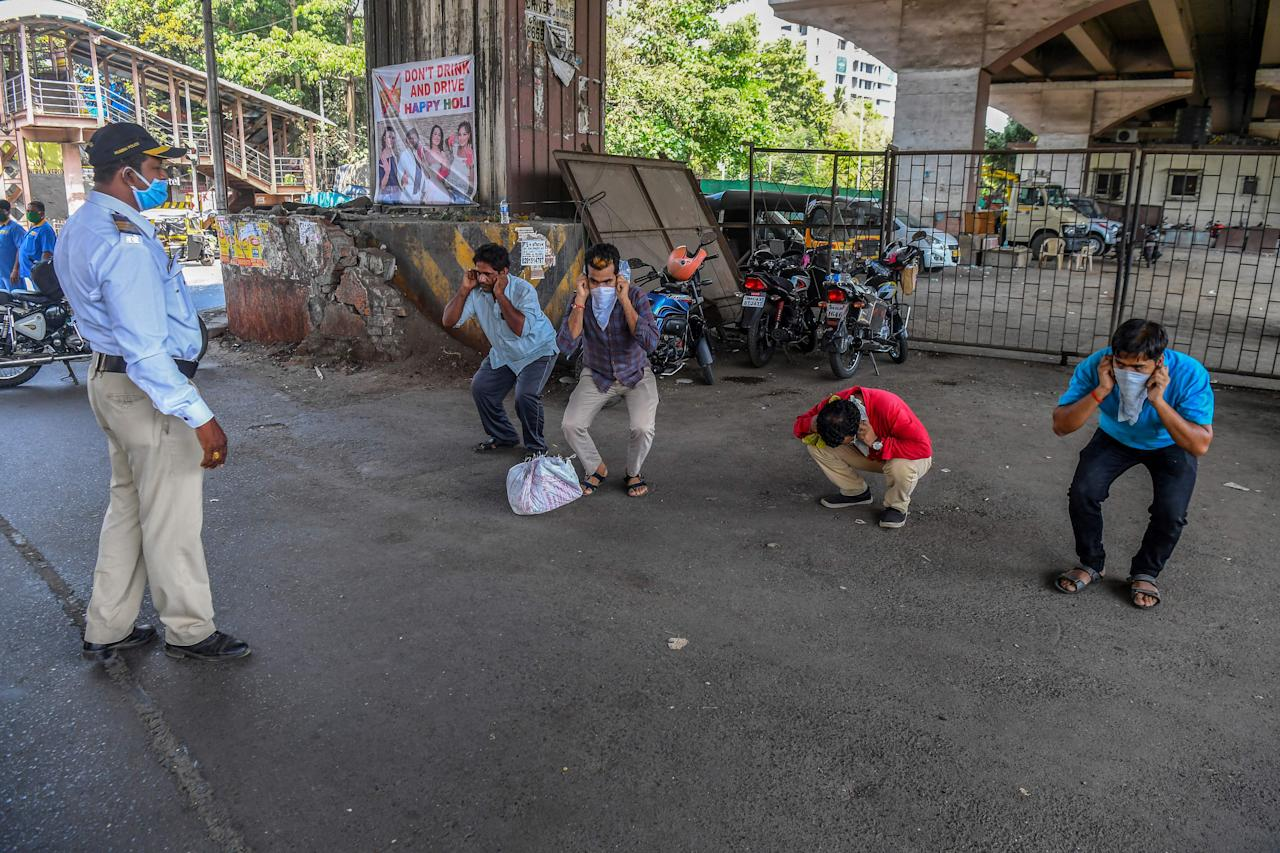 A policeman (L) asks people to do sit-ups as punishment for going out without a valid reason during a government-imposed nationwide lockdown as a preventive measure against the COVID-19 coronavirus, in Mumbai on March 31, 2020. (Photo by INDRANIL MUKHERJEE / AFP) (Photo by INDRANIL MUKHERJEE/AFP via Getty Images)