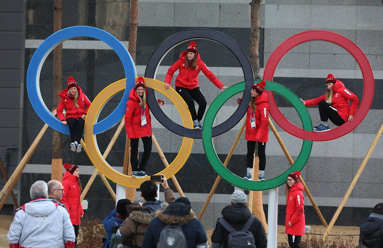 Swiss athletes poseinside the Olympic rings in Pyeongchang, South Korea, on Feb. 8, 2018. (Photo: Steve Russell via Getty Images)