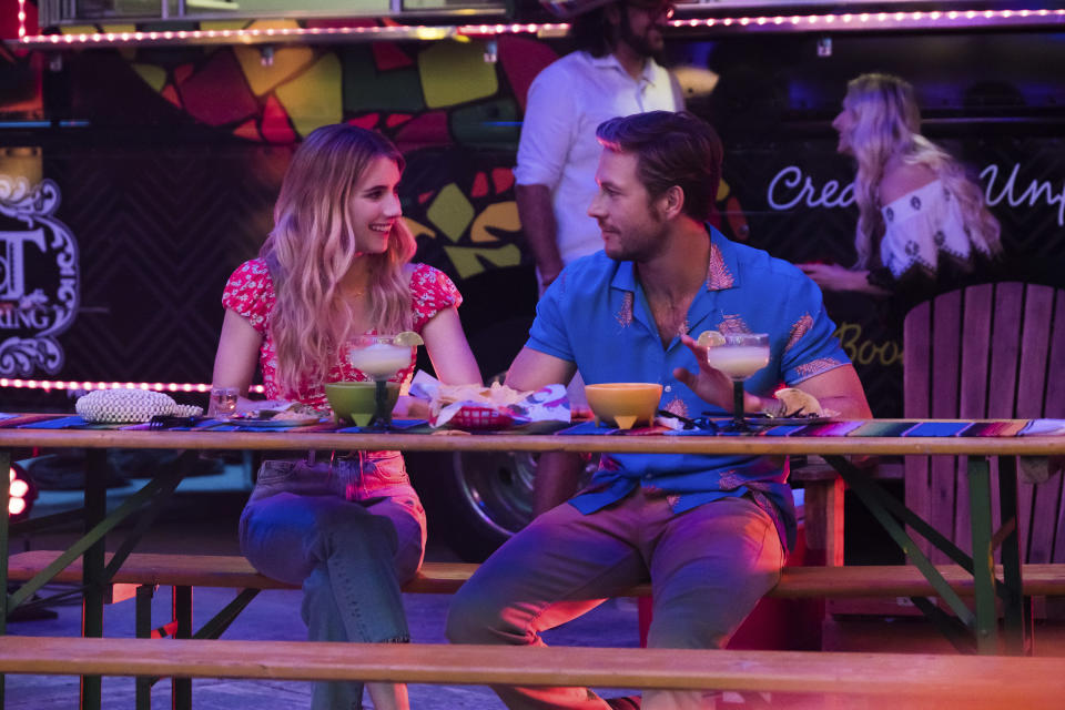"This image released by Netflix shows Emma Roberts and Luke Bracey, right, in a scene from ""Holidate."" (Steve Dietl/Netflix via AP)"