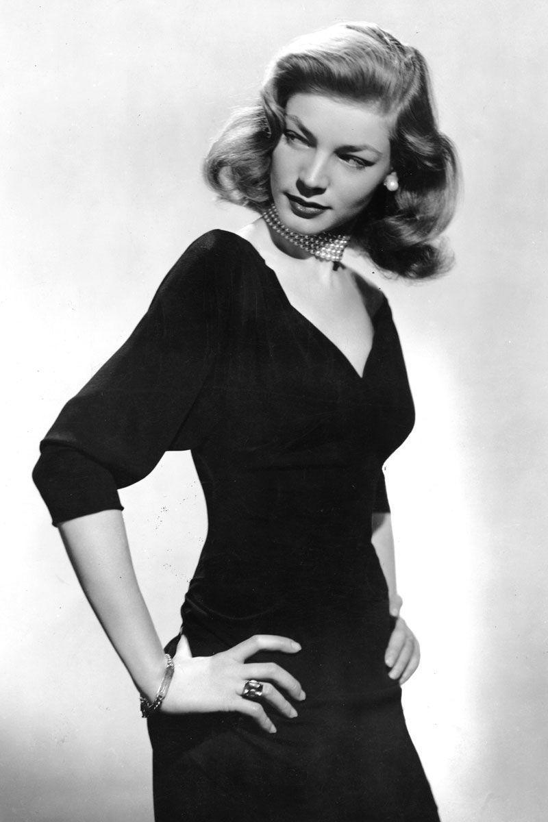 <p>Lauren Bacall dresses up her v-neck LBD with a four-strand pearl choker and, of course, her killer stare. </p>