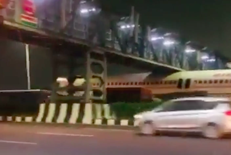 The plane became wedged under the bridge from its wings. (SWNS)