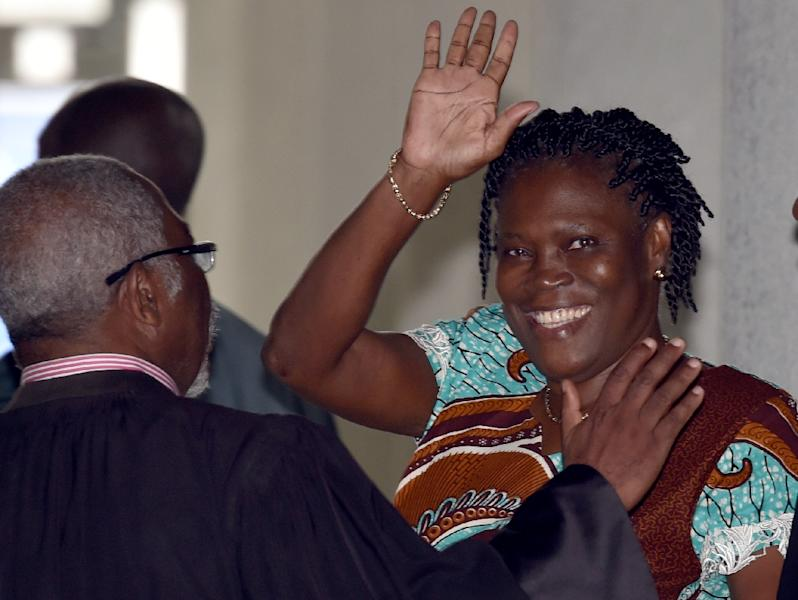 """Ivorian former first lady Simone Gbagbo waves as she arrives at the Court of Justice in Abidjan for her trial for """"attempting to undermine the security of the state"""" in events leading to a bloody 2010-2011 post electoral crisis, February 23, 2015 (AFP Photo/Issouf Sanogo)"""