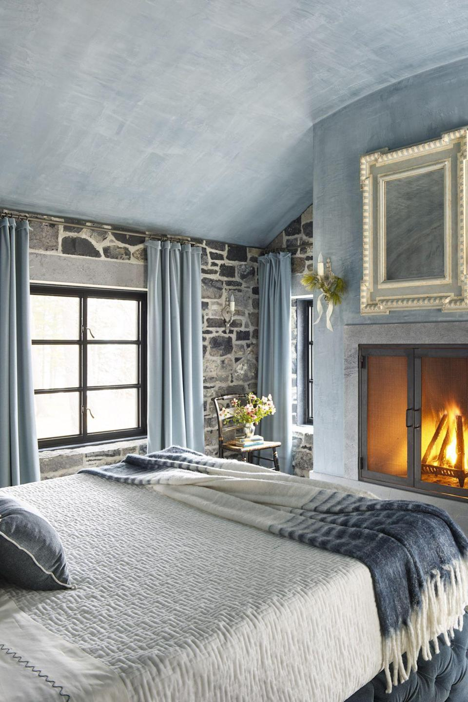 <p>Nothing makes a home homier than a roaring fireplace. If you're lucky enough to have one in the main bedroom, beautify the area around it with a large mirror. We also love the textured blue ceiling and accent wall—it adds a softer touch to the rustic stone wall. </p>