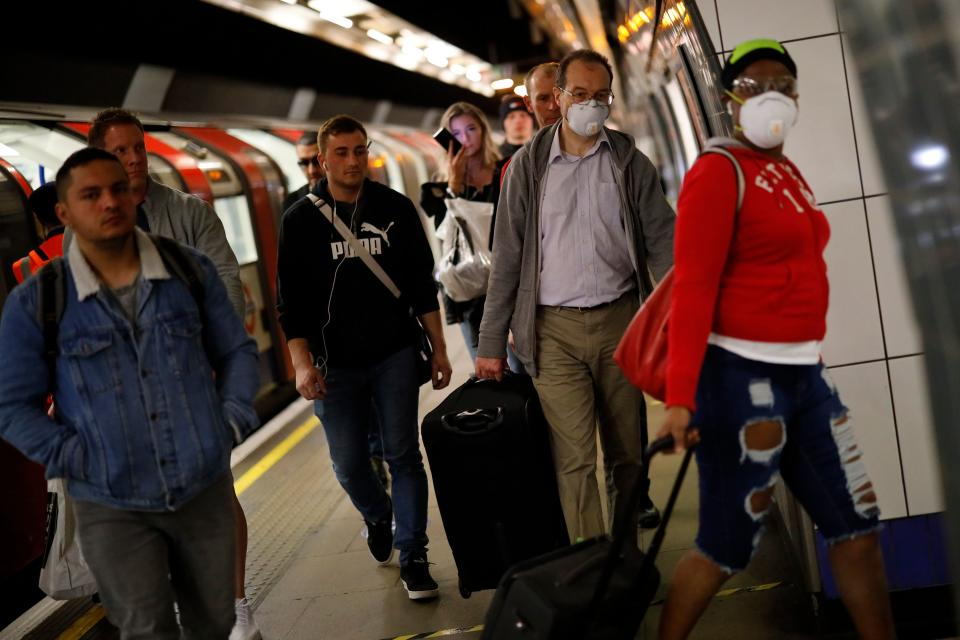 Commuters, wearing PPE (personal protective equipment) as a precautionary measure against COVID-19, walk along the platform at a tube station in London on April 22, 2020, as Britain remains under lockdown during the novel coronavirus COVID-19 pandemic. - British Prime Minister Boris Johnson tentatively began his return to work on Tuesday after being hospitalised for coronavirus, as parliament returned and criticism grew over the government's response to the outbreak. (Photo by Tolga Akmen / AFP) (Photo by TOLGA AKMEN/AFP via Getty Images)