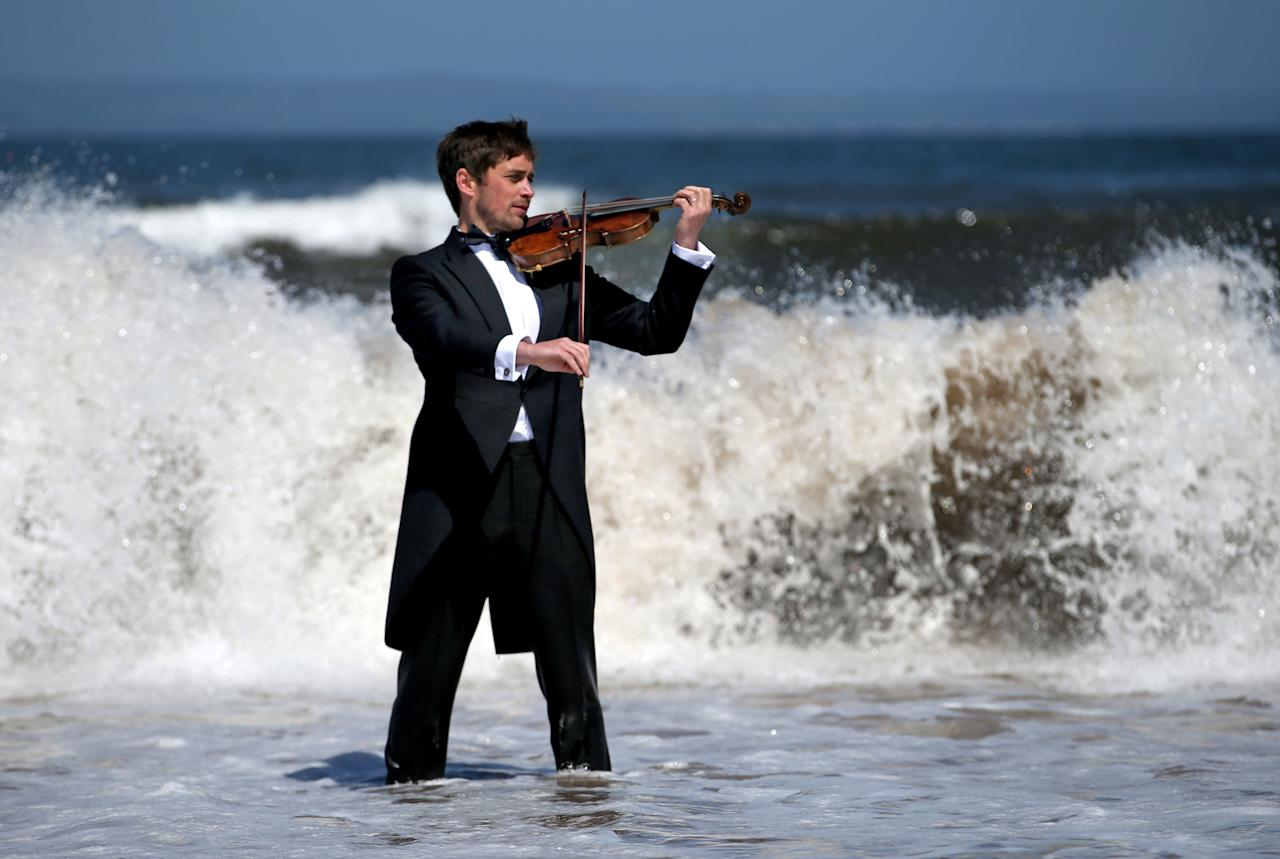 <p>Musician Thoren Ferguson plays the Il Mare Violin, which is made from driftwood in the sea at Yellowcraigs, East Lothian. (PA) </p>