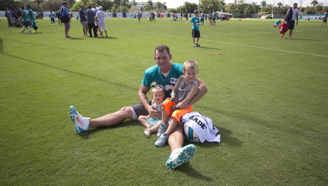 Miami Dolphins' Jason Trusnik poses for family photos with his children, Ava and Austin, after an NFL football training camp Friday, July 25, 2014, in Davie, Fla. (AP Photo)