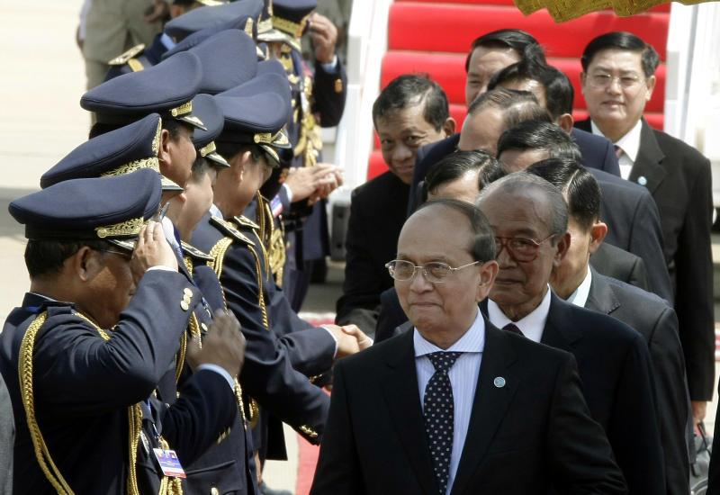 Myanmar President Thein Sein, center, walks upon his arrival at Phnom Penh International Airport in Phnom Penh, Cambodia, Wednesday, March 21, 2012. (AP Photo/Heng Sinith)