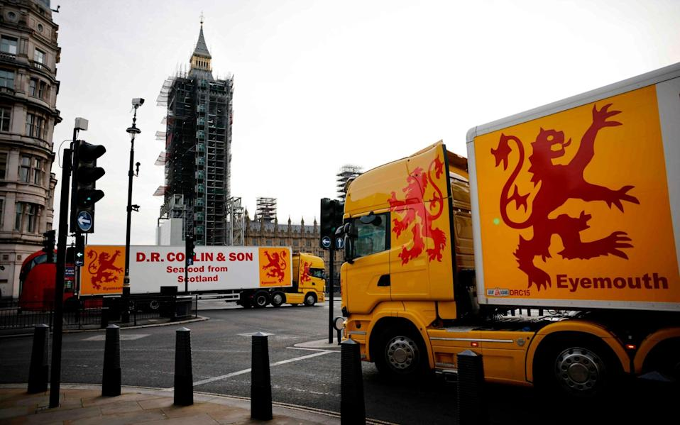 Lorries from Scotland drive past the Houses of Parliament in a protest action by fishermen against post-Brexit red tape and coronavirus restrictions - AFP