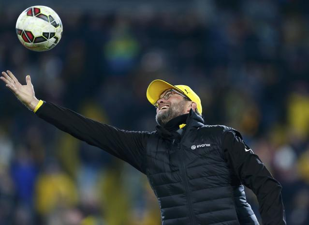 Borussia Dortmund's coach Juergen Klopp catches a ball as his team's warm up before their German Cup (DFB Pokal) soccer match against Dynamo Dresden in Dresden March 3, 2015. REUTERS/Hannibal Hanschke (GERMANY - Tags: SOCCER SPORT) DFB RULES PROHIBIT USE IN MMS SERVICES VIA HANDHELD DEVICES UNTIL TWO HOURS AFTER A MATCH AND ANY USAGE ON INTERNET OR ONLINE MEDIA SIMULATING VIDEO FOOTAGE DURING THE MATCH.