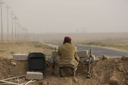 A Kurdish fighter keeps guard while overlooking positions of Islamic State militants near Mosul in northern Iraq