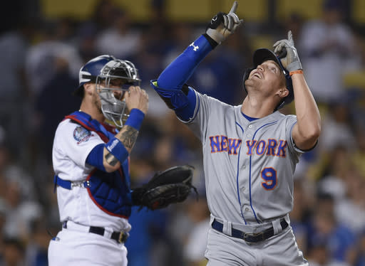 New York Mets' Brandon Nimmo, right, celebrates while crossing home plate after hitting a three-run home run during the ninth inning of a baseball game as Los Angeles Dodgers catcher Yasmani Grandal looks on in Los Angeles, Monday, Sept. 3, 2018. The Mets won 4-2. (AP Photo/Kelvin Kuo)