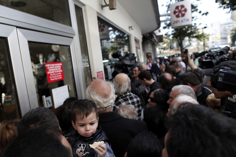 FILE - In this Thursday, March 28, 2013 file photo, people wait outside a branch of Laiki Bank in Nicosia. Engineering a financial bailout for Cyprus in March 2013 was such a chaotic process that top European officials say it is time to rethink how the region manages its crisis _ and who should be involved. Officials say the International Monetary Fund, which has contributed financial expertise and billions in emergency loans, may no longer be needed as a key decision-making partner. And they say that the eurozone would be able to make decisions and take action more quickly if it wasn't bound by the need for unanimous agreement among its 17 member countries. (AP Photo/Petros Giannakouris, File)