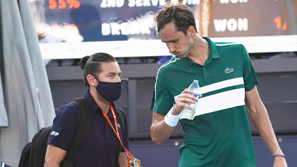 Daniil Medvedev (pictured right) drinking some water and talking to the trainer.