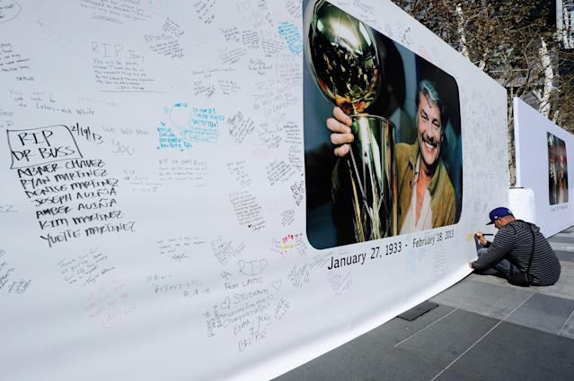 LOS ANGELES, CA - FEBRUARY 20: Lakers fan Paul Carillo writes a personal message on the Dr. Buss Memorial Banners in the Nokia Plaza at L.A. Live, directly across the street from Staples Center on February 20, 2013 in Los Angeles, California. The Lakers will hold a memorial service to celebrate the life of longtime owner Jerry Buss at the Nokia Theater on Thursday, for invited guests only. Dr. Buss died at the age of 80 on Monday following an 18-month battle with cancer. (Photo by Kevork Djansezian/Getty Images)