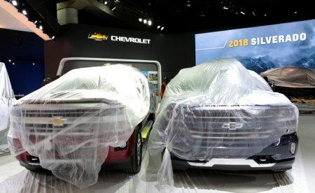 Two 2018 Chevrolet Silverado pick-up trucks sit under plastic on the display floor before the start of Press Days for the North American International Auto Show at Cobo Center in Detroit, Michigan, U.S., January 12, 2018. REUTERS/Rebecca Cook