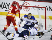 St. Louis Blues' Jay Bouwmeester, right, dives in front of the puck as goalie Jake Allen, center, and Calgary Flames' Elias Lindholm, of Sweden, watch during the second period of an NHL hockey game Saturday, Dec. 22, 2018, in Calgary, Alberta. (Jeff McIntosh/The Canadian Press via AP)