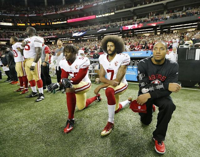 Colin Kaepernick and 49ers linebacker Eli Harold (L) kneel during the playing of the national anthem before a game last season. (AP)