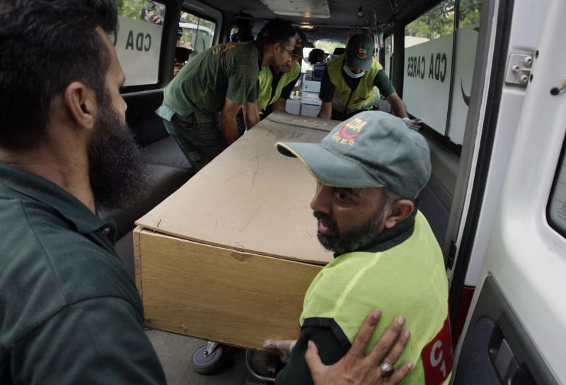 Pakistani rescue workers unload the casket of a foreign tourist, who was killed by Islamic militants, from an ambulance to shift in a morgue of local hospital in Islamabad, Pakistan, Sunday, June 23, 2013. Islamic militants wearing police uniforms shot to death nine foreign tourists and one Pakistani before dawn as they were visiting one of the world's highest mountains in a remote area of northern Pakistan that has been largely peaceful, officials said. (AP Photo/Anjum Naveed)